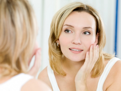 Eine Frau blickt in den Spiegel und betrachtet ihre Haut. Ihre Haare sind blond und ihre Augen grün.
