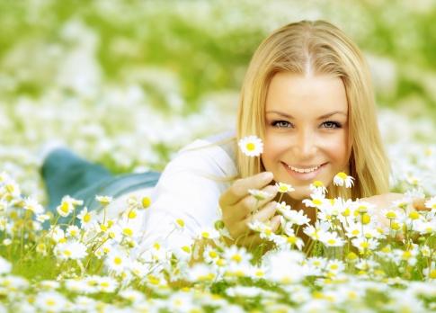 Frau liegt in der Wiese und riecht an Kamille