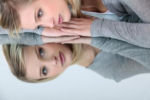 Eine Frau blickt mit einem geneigten Kopf auf die spiegelnde Oberfläche eines Tisches und überlegt, wie sich sich selbst wertschätzen kann.