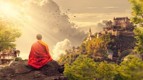 Ein Mönch sitzt auf einem Berg und sieht zum Kloster