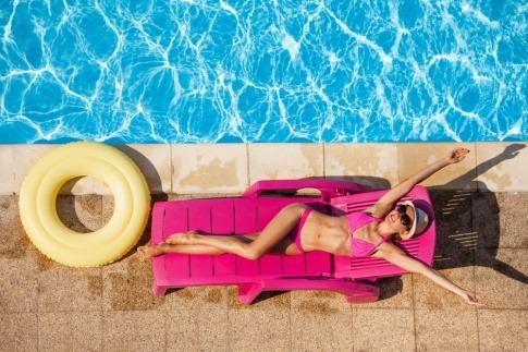 Frau am Pool beim Sonnen