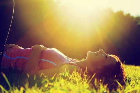 Eine Frau liegt im Gras bei Sonnenschein