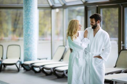 Ein Mann und eine Frau tragen einen Bademantel im Spa Bereich