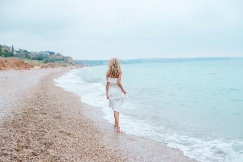 Eine Frau geht am Strand spazieren