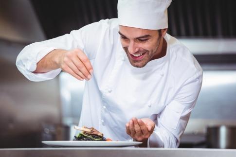 Ein Koch würzt Speisen