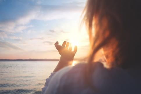 Eine Frau steht vor einer Sonne