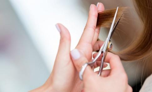 Ein Friseur schneidet die Haarspitzen einer Frau.