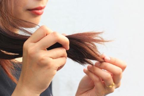 Eine Frau betrachtet Spliss in den Haaren