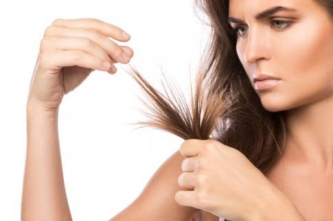 Eine junge Frau schaut sich verärgert ihre von Spliss betroffenen Haarspitzen an.