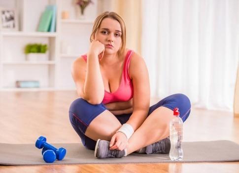 Eine leicht demotiviert dreinblickende Frau im Sportoutfit sitzt im Schneidersitz auf einer Sportmatte und ruht ihren Kopf auf dem angewinkelten rechten Arm. Neben ihr liegen Hanteln.