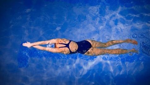 Eine Aufnahme aus der Vogelperspektive auf eine Frau, die in einem Swimmingpool schwimmt.