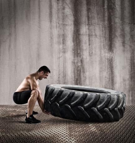 Ein Mann versucht einen riesigen Reifen zu heben