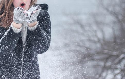 Eine Frau mit starkem Immunsystem bläst im Winter Schnee von den Händen