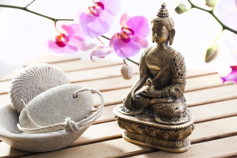 Eine kleine Statue steht neben zwei Steinen als Symbol für Ayurveda