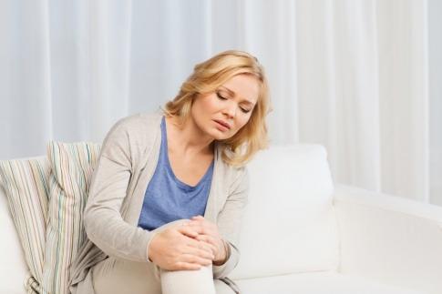 Frau mit steifen Gelenken nach dem Sitzen hält sich das Knie