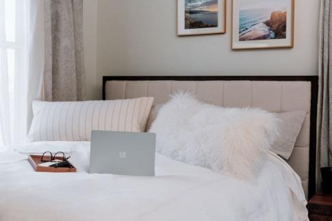 Auf einem Bett liegt ein Laptop als Störquelle im Schlafzimmer