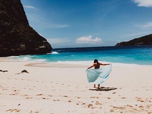 Eine modisch gekleidete Frau geht den Strand entlang
