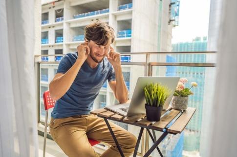 Ein junger Mann sitzt am Balkon und hält sich die Ohren zu
