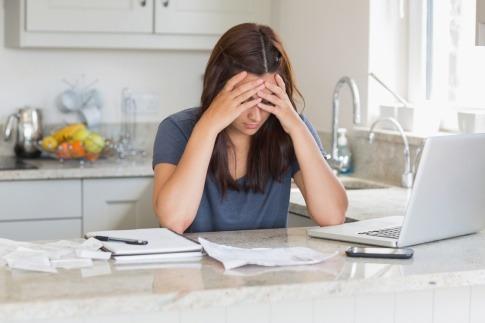 Eine Frau sitzt gestresst beim Laptop in einer Küche
