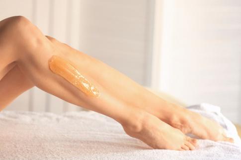 Eine Frau hat eine Sugaringpaste auf den Beinen
