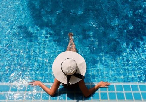 Frau mit Hut am Rand des Pools