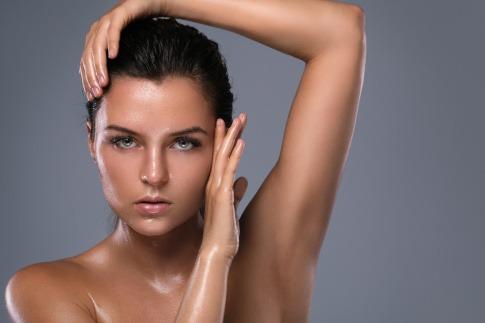 Eine Frau hat fettige Haut und sollte Talgproduktion reduzieren