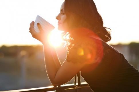 Eine Frau hält eine Teetasse und schaut glücklich aus