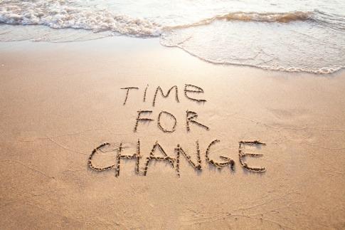 Auf einem Strand steht im Sand Time for Change