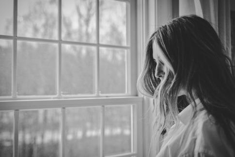 Eine Frau versucht sich im Trauer überwinden, indem Sie vor einem Fenster steht und weint.