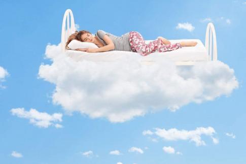 Frau im Bett auf Wolken