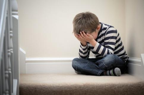 Ein kleiner Junge sitzt den Kopf in die Hände gestützt auf einer Treppe
