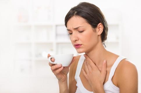 Eine Frau hat Halsschmerzen durch trockene Atemwege