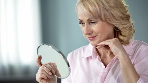 Eine Frau mit trockener Haut im Alter schaut in den Spiegel