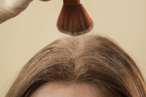 Eine Frau gibt selber gemachtes Trockenshampoo auf die Haare