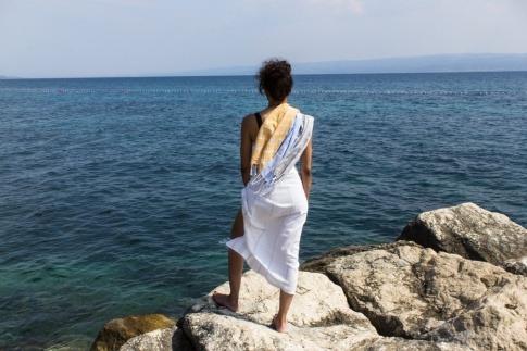 Frau steht in einem Tuch das im Wind weht