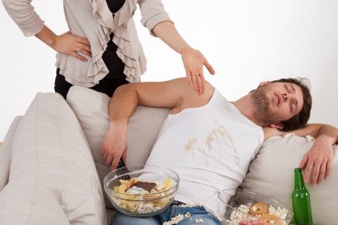 Ein Mann schläft mit Essen auf der Couch