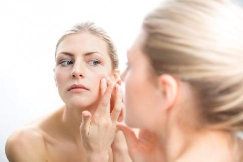 Eine Frau betrachtet ihre unreine Haut
