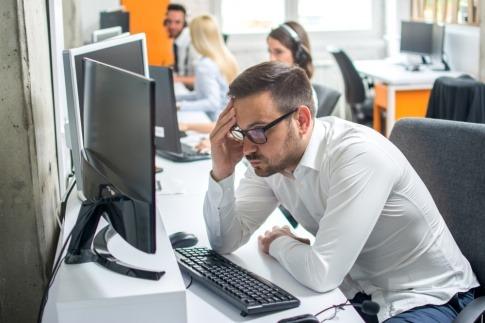 Ein junger Mann auf der Arbeit schaut gestresst auf seinen PC-Bildschirm