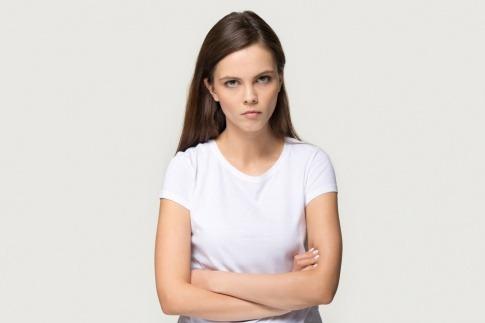 Eine Frau mit unzufriedenem Gesicht und verschränkten Armen