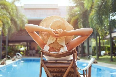 Eine Frau sitzt entspannt im Urlaub mit einem Beauty Bag