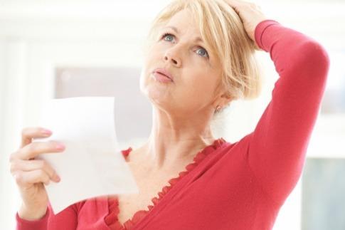 Eine Frau hält einen Zettel und scheint vergessen zu haben