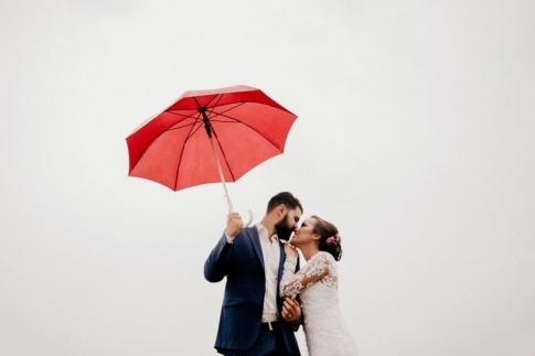 Ein Mann küsst eine Frau, in der Hand einen Regenschirm, um Sicherheit zu vermitteln