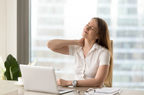 Frau greift sich an den schmerzenden Nacken