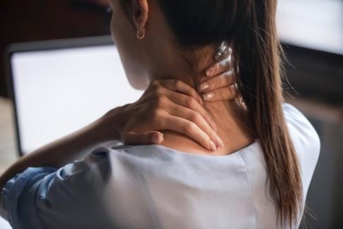 Frau im Homeoffice reibt sich die verspannten Schultern
