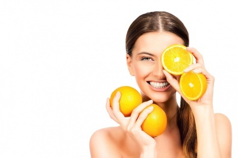 Frau mit Orangen vor dem Gesicht.