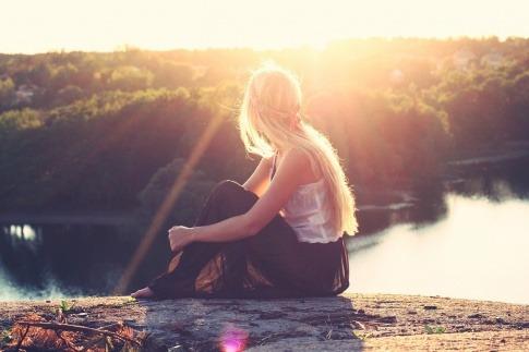 Junge Frau sitzt in der Sonne und kann Vitamin D Mangel beheben