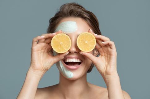 Eine Frau mit Kosmetik im Gesicht hält Vitamine von Orangen als Radikalfänger vor die Augen