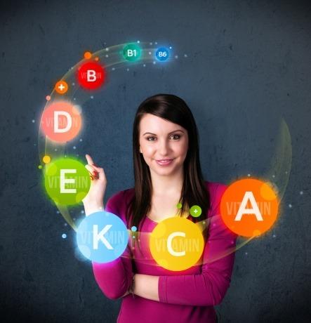 Eine junge Frau um deren Kopf sich kleine Kreise als Symbole für verschiedene Vitamine drehen.