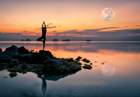 Eine Frau macht bei Vollmond im Juli Yoga