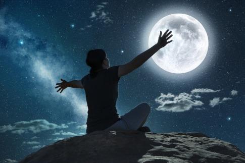 Eine Frau plagt bei Vollmond schlechter Schlaf, sie sitzt nachdenklich auf einer Klippe und blickt zum Mond.